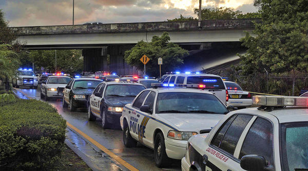 K9 police cars from various south Florida agencies gather on westbound Pembroke Road, after a police involved shooting on the Florida Turnpike.