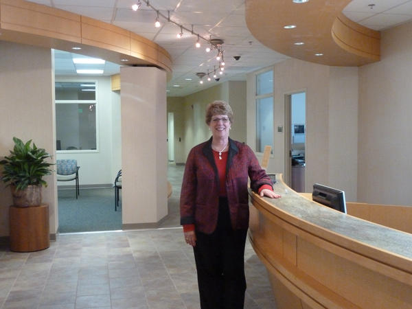 Executive Director Barbara Levy Gradet stands next to the reception area of the new Jewish Community Services offices located inside Jewish Community Center in Owings Mills.