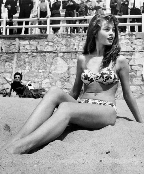 French actress Brigitte Bardot sitting on the beach during the Cannes Film Festival in 1953.
