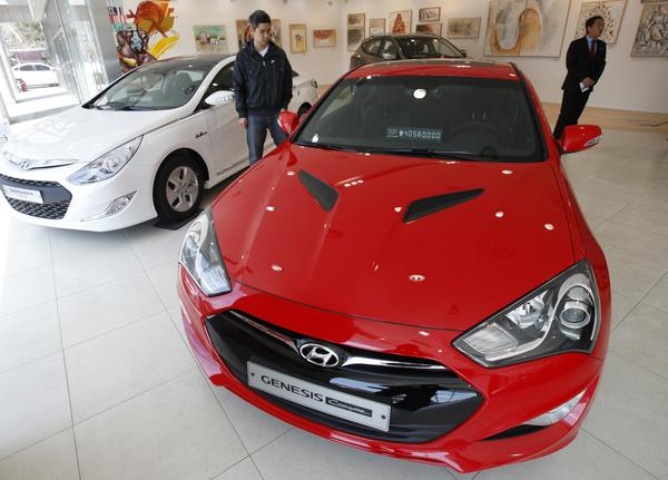 People look around as Hyundai Motor's Genesis (front) and Sonata are displayed at a gallery-style Hyundai dealership in Seoul
