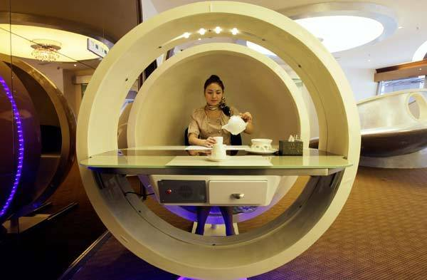 A waitress poses inside an egg-shaped dining booth at an A380 theme restaurant during a media event before its official opening. Special Class, the name of the restaurant, can serve up to 110 customers, local media reported. The restaurant officially started business on May 1, 2012.