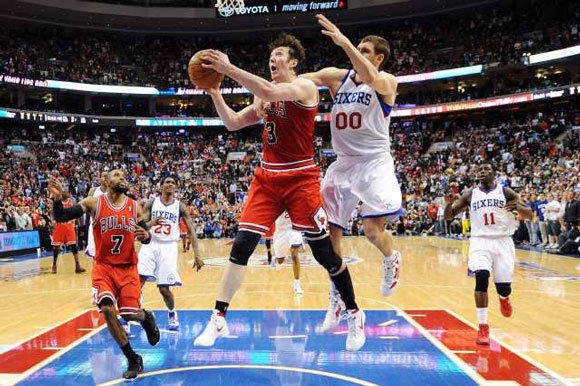 Omer Asik of the Bulls is fouled by Spencer Hawes of the 76ers near the end of Game 6.