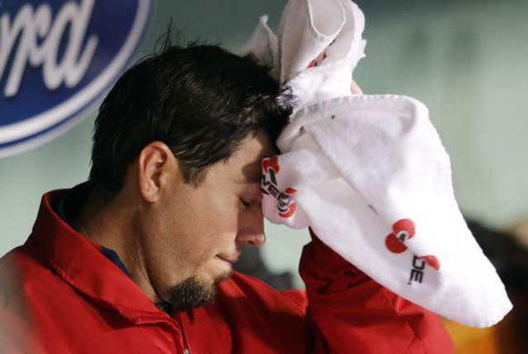 Josh Beckett wipes his head in the dugout after being taken out in the third inning.