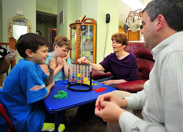 The Malott family often plays board games together as a family activity. From left are Luke, 7, Sara, 9, Melinda and Jason. Melinda has chronic fatigue syndrome but says she has adapted to living as normal a life as possible.