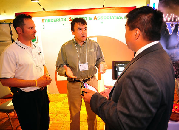 Dave Trostle, left, and Tony Taylor, center, of Frederick, Seibert & Associates chat with Verizon's Michael Tambaoan Friday during the Hagerstown-Washington County Chamber of Commerce Business Expo at Hager Hall.