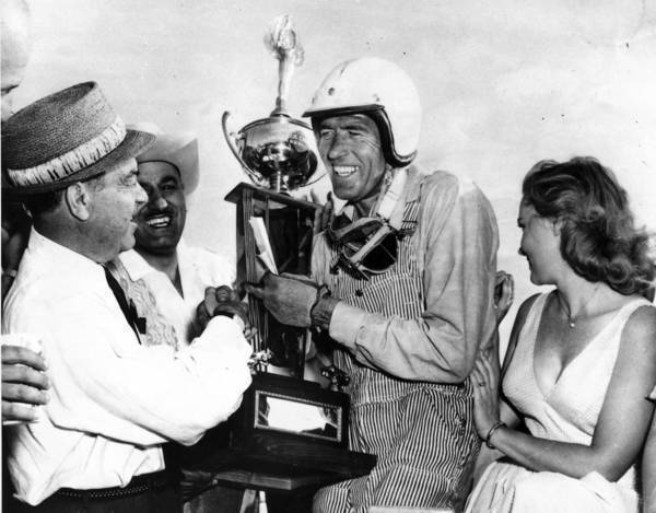 Carroll Shelby accepts the winner's trophy at Riverside International Raceway after winning the 200-mile International Grand Prix in 1960.