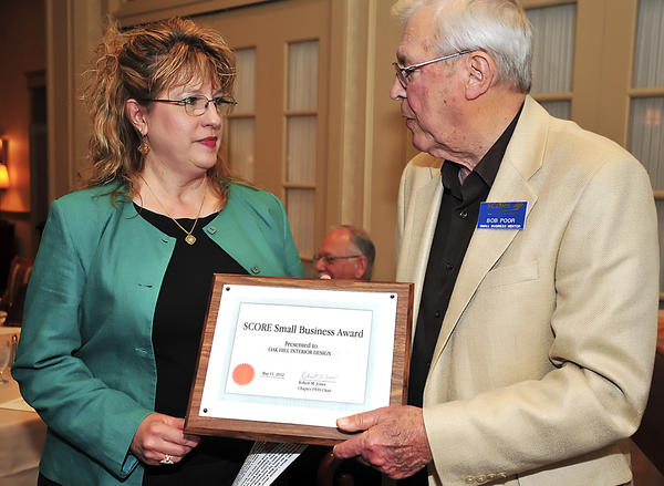 Vickie Hrabal, owner of Oak Hill Interior Design in Hagerstown, receives the SCORE Small Business Award Friday night from Bob Poor, SCORE small business mentor. The award was presented at the SCORE Small Business Awards dinner at Fountain Head Country Club.