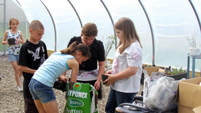 Elementary student Sidney Stutzman reaches into a bag of potting soil alongside Gabe Manthey, Brittany Sleasman and Kelsey Watkins while Kara Platt (background) carries a tomato plant. Shanksville-Stonycreek School District unveiled the $20,000 greenhouse on Friday.