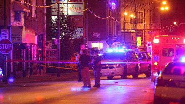 Police investigate the scene of a shooting where one person died and three others were wounded May 11.