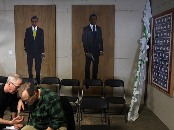 Paintings of Mayor Rahm Emanuel and President Barack Obama, both holding handguns, stand guard during an anti-NATO workshop today for members of Occupy Chicago at their temporary headquarters near Chinatown.