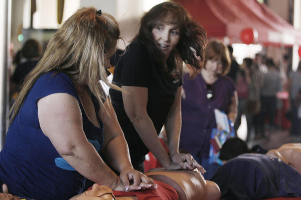 Registered nurse Susan Hayward, right, shows how to do CPR during Fire Service Day in Burbank on Saturday, May 12, 2012.