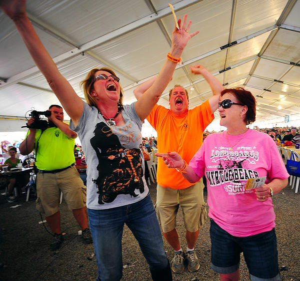 "Jeanne Kates, left, reacts to winning a drawing for $10,000 Saturday at Bonanza Extravaganza, and Linda Fisher congratulates her. Jeanne needed a ""four"" and Linda hoped for a ""one"" as the fourth and final ball was selected. Kates came from Perryville, Md. and Fisher is a Frederick resident. Bonanza Extravaganza chairman Rick Conrad is happy for the winner."