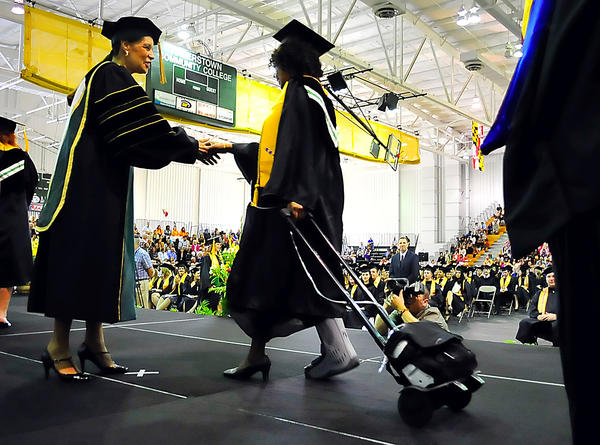 Merna Pettit gets a congratulatory handshake from Hagerstown Community College board of trustees president Carolyn Brooks Saturday during commencement. Graduate Pettit wheeled an oxygen tank across the stage. She suffers from pulmonary fibrosis and lupus.