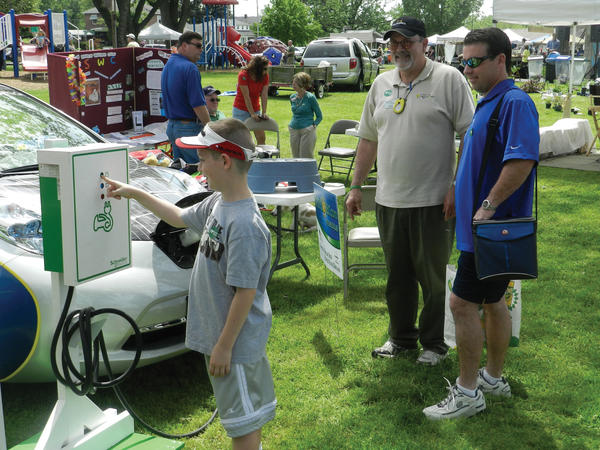 Donovan Kisner, 9, of Boonsboro, pushes the button to activate the charger for a solar-powered car on Saturday at Boonsboro Green Fest at Shafer Memorial Park. Also pictured are John Christensen of mtvSolar in Berkeley Springs, W.Va., and Donovan's father, Michael Kisner.