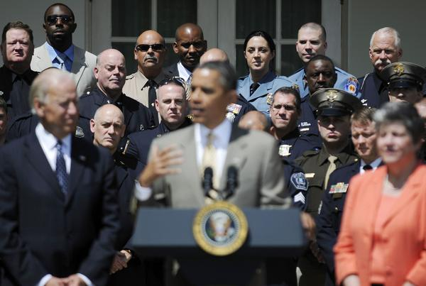 Top Cops award winners listen to remarks by U.S. President Barack Obama (C, foreground) in the Rose Garden at the White House. Standing with Obama are Vice President Joe Biden (L) and Homeland Security Secretary Janet Napolitano (R).