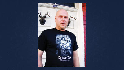 Blair Murphy stands in front of the Grand Midway Hotel in Windber. Murphy's Draculacon IV will take place at the hotel on Saturday. Murphy's wearing an event t-shirt designed by artist Michael Mararian.