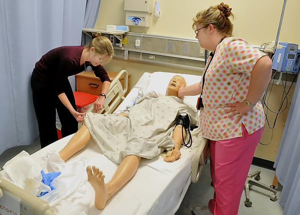 Peggy Scibelli, left, of Walkersville, Md., gives an IV to a medical mannequin as Hagerstown Community College Nursing Professor Lori Manilla looks on.