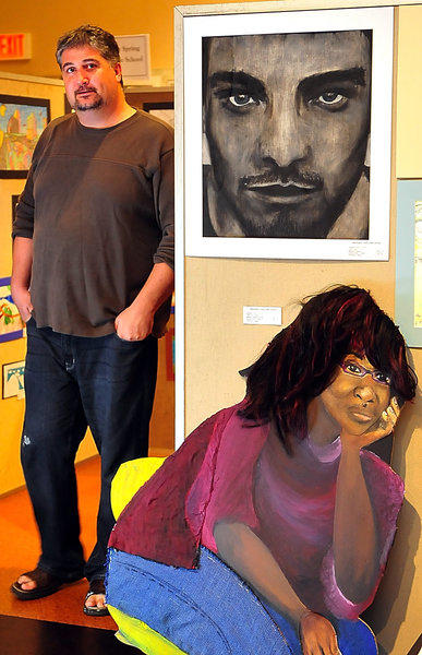 Philip Shaer rounds a corner in Washington County Museum of Fine Arts where middle and senior high school art students have their works displayed. He is an art teacher at E. Russell Hicks Middle School. The pieces in the foreground are by South Hagerstown High School students.