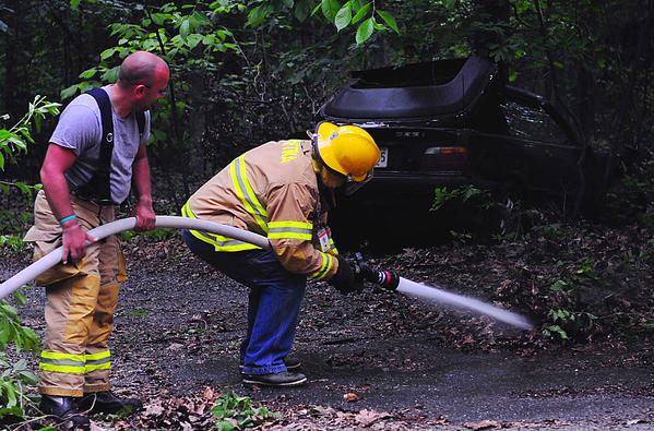 Mt. Aetna Volunteer Fire Department volunteers Chris Macomber, left, and Dale Martin hose away residue at an accident scene on Crystal Falls Drive Sunday night.
