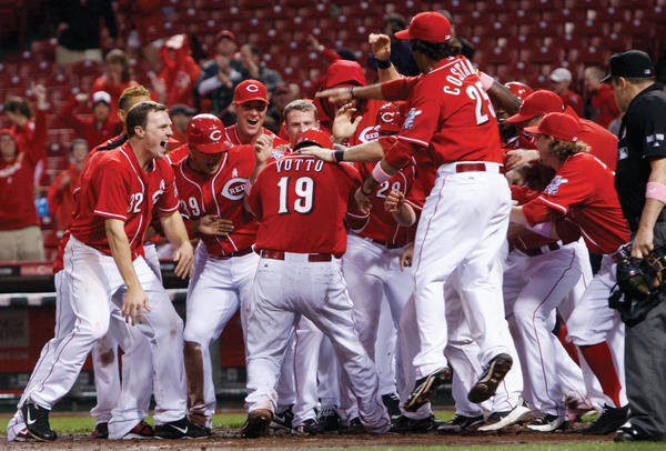 Cincinnati's Joey Votto (19) is mobbed at the plate after hitting a grand slam off Washington relief pitcher Henry Rodriguez in the bottom of the ninth inning Sunday in Cincinnati.