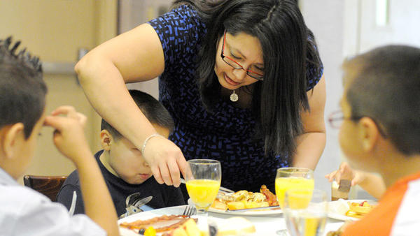 Niza Saldana cuts food for her son Bryan Ojeda, 4, during the Mother's Day Brunch at the Barbara Worth Country Club Sunday.