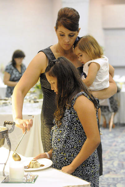 Diana Renteria helps her daughter Alexia Renteria, 9, get her plate while holding Allison Nunez, 2, during the Mother's Day Brunch on Sunday at the Barbara Worth Country Club.