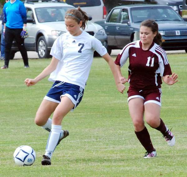 Petoskey's Emily Eberhart (7) clears the ball away from Charlevoix's Katie Kiteley during Saturday's Petoskey Girls' Soccer Invitational at the Click Road Soccer Complex.