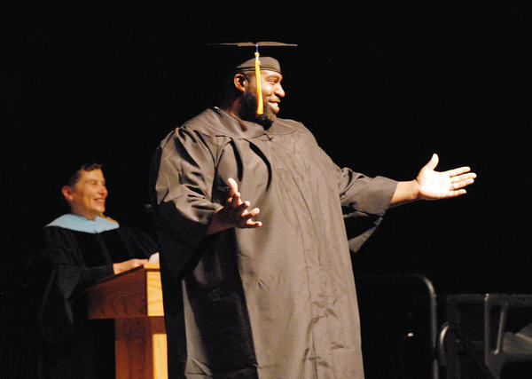 North Central Michigan College student Fred Howard Alexander III acknowledges family and friends while crossing the stage to receive his diploma. Alexander graduated with an associate of general studies.