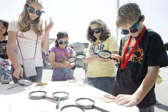 Sara Hersh, 12, from left, Samantha Cook, 10, Tina Tchakian, 14, and Ayden Blackwood, 11, burn a piece of wood with a magnifying glass at Solar Discovery Faire 2012, which took place at Keppel Elemantary School in Glendale.