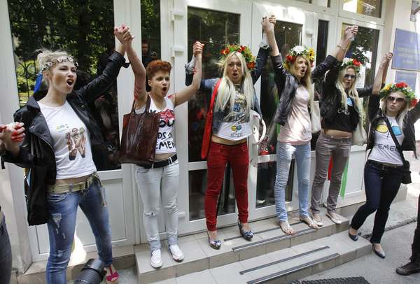 Activists of Ukrainian women's rights group Femen shout slogans as they arrive to court hearings in two criminal cases, first of the kind to be launched against the movement famous for its topless public protests.