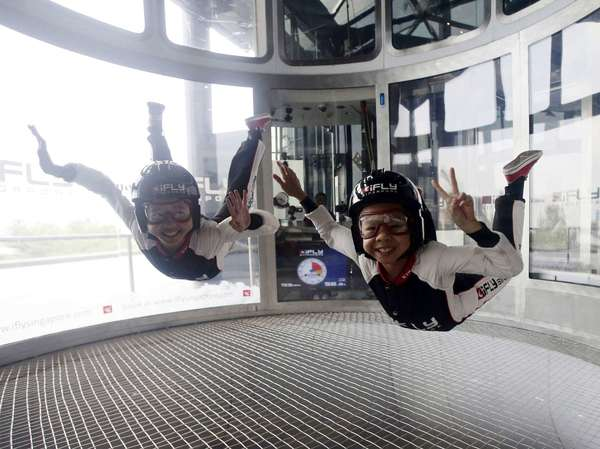 Indoor skydivers 10-year-old Kyra Poh (R) and 11-year-old Choo Yixuan, both of Singapore, greet the media during an indoor skydiving session for a media event at iFly Singapore on Sentosa Island.