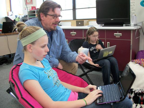 Jim Tisdel coaches Pellston Middle School students Emma Robbins on her digital arts project as student Taylor Myroniuk works in the background. The digital media class is part of the Crooked Tree Arts Center 21st Century after-school arts program.