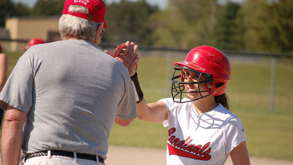 Katie Kierczynski gives a high five to assistant coach Jim Dixon during J-L's softball sweep against Boyne City Monday.