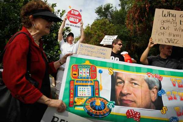 Protesters hold a banner featuring JPMorgan Chairman and CEO Jamie Dimon outside the annual shareholders meeting in Tampa, Fla. JPMorgan Chase, the largest U.S. bank, last week disclosed a $2-billion trading loss.