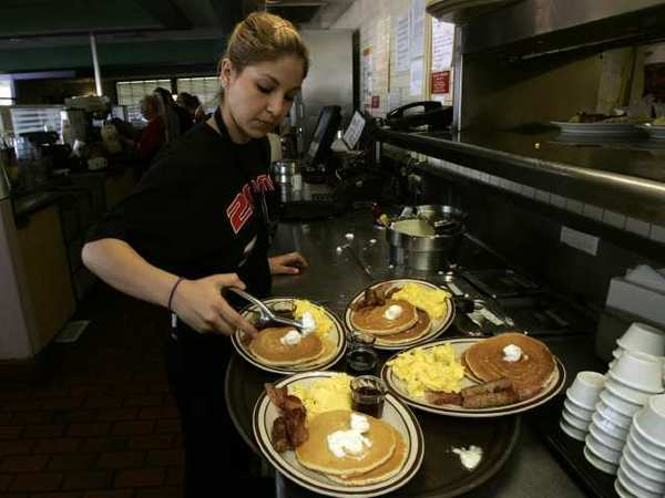 Gaby Estrella prepares breakfast orders at a Denny's in Santa Ana. The chain pledged to try to wean its suppliers off of gestation crates for pigs.