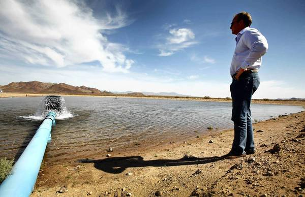 Scott Slater, president and general counsel of Cadiz Inc., watches as water pours into a spreading basin