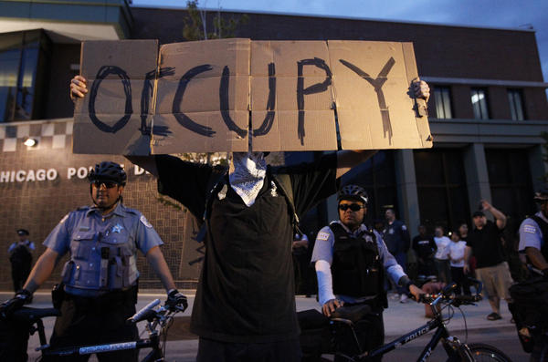 A protester shouts at members of the Chicago police department outside their station at 32nd and Halsted Streets.