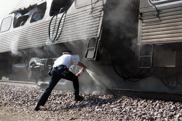 A conductor uses a fire extinguisher on the undercarriage of a Metra train involved in a collision with a truck in Mt. Prospect on Friday, May 13, 2011.   (Photo by Johannes Arndt)