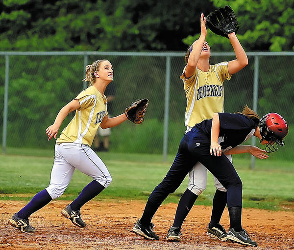 Smithsburg's Krystal Holl reaches up to make a catch over Manchester Valley baserunner Katie Cullum while Karah Knight backs up the play. The Leopards defeated Manchester Valley 6-0 in the Maryland Class 1A West East Sectional semifinals.