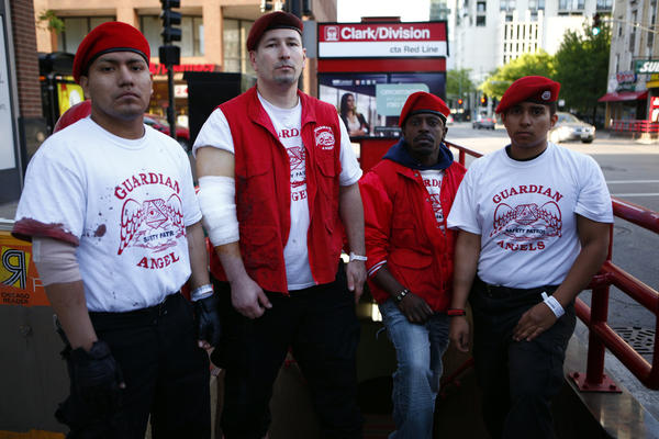 Guardian Angels members (from left) Erik Eulogio, Michael Fuentes, Thomas Hunt and Mario Rodriguez outside the CTA Red Line Clark and Division Stop early Wednesday, after having stab wounds treated at the hospital. They were stabbed while holding down a man who pistol-whipped a CTA rider.