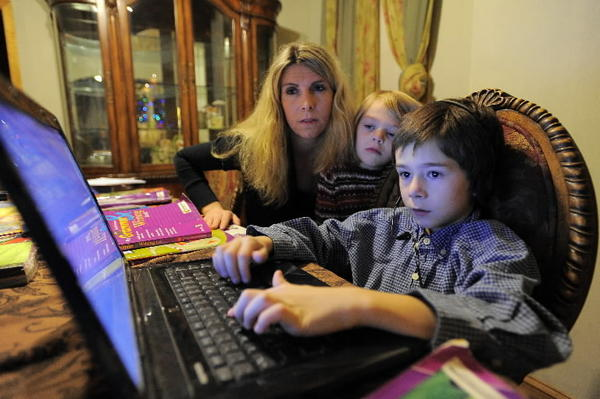 12/03/2011 -- Amy Sparks and daughter Samantha, 5 watch Patrick Sparks, 8 work on an online English lesson at the Sparks home Thu, Dec. 1, 2011. (Karl Merton Ferron / Baltimore Sun Staff)