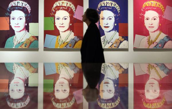 A woman walks past silkscreen prints of Britain's Queen Elizabeth by Andy Warhol during a press view at the National Portrait Gallery in London.