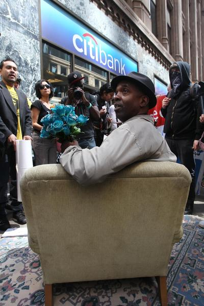 Loren Taylor sits in a makeshift living room outside a Citibank branch at LaSalle and Madison streets. The furniture was set up at the bank after a group of about 130 protesters marched north through the Loop from the Board of Trade.
