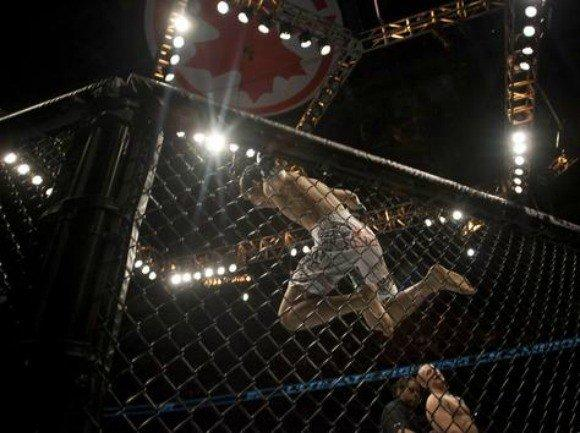 """Korean Zombie"" Chan Sung Jung jumps for joy after defeating Mark Hominick, lower right, during UFC 140 in Toronto on Dec. 10, 2011."