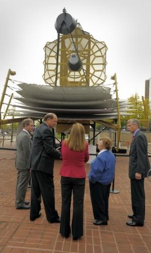 U.S. Sen. Barbara A. Mikulski, second from right, and others listen to Northrop Grumman Space Technology Vice President Jeff Grant, second from left, beneath a full-scale model of the James Webb Space Telescope at the Maryland Science Center.