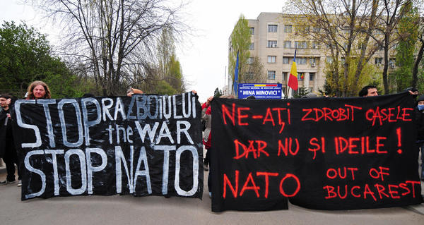 Some fifteen people take to the streets of southern Bucharest holding banners reading (at left) 'Stop the War, Stop NATO' and (at right) 'You crush our bones but not our spirit' as they protest against the North Atlantic Treaty Organisation (NATO) on the second day of the NATO summit in Bucharest on April 3, 2008.