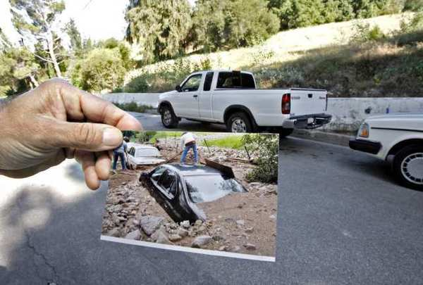 Local resident Gilbert Jacobi, who is happy to have the K-rails in front of his home on the 5400 block of La Forest Drive in La Canada Flintridge, shows photos of his cars that were covered by mudflows during the 2010 storms.