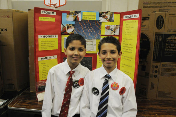 Jadiel Crespo, 10, left, and Gabriel Rivera, 11, right, fourth graders at Maria Sanchez School, pose in front of their project on the absorption of oil spills on water during the judging of the 21st annual city-wide science fair held at Annie Fisher School Wednesday.