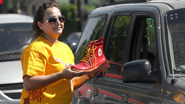 Janet Vasquez uses a red shoe to collect donations from motorists during Ronald McDonald House's Red Shoe Day at Main and Eighth streets Wednesday in El Centro. Imperial Valley crew committee member Elia Fuentez said other volunteers also collected donations in Brawley, Imperial, Holtville and Calexico.