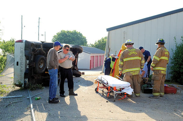 Clark County Deputy Sheriff Johnny Graves, second from left, takes information from Ward Ramsey, manager of Storage Rentals of America, Rockwell Road, after a vehicle crashed through the fence and into one of the storage buildings Wednesday morning. Winchester Fire-EMS and Clark County Fire Department crews treat the victim, Joseph Hensley of 250 Oxford Drive, at right. Hensley was transported to Clark Regional Medical Center. The vehicle was traveling east when it left the road and crashed through the fence, striking one of the storage buildings.